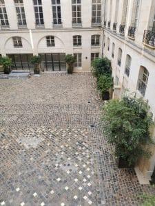 Cour pavée d'un immeuble parisien avec clous de chaussée laiton
