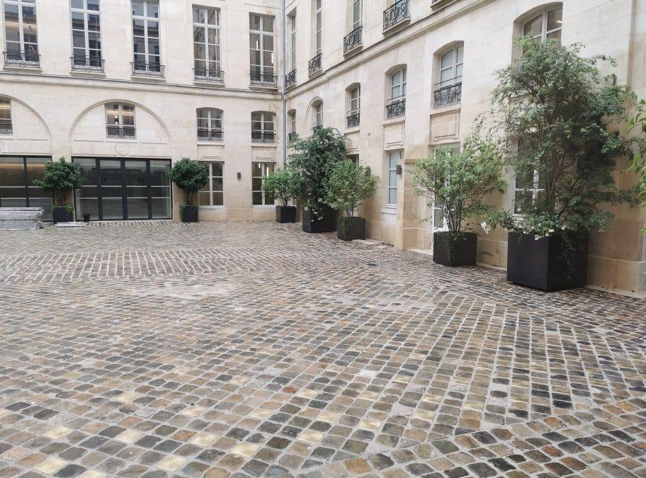 Cour pavée dans immeuble parisien ornée de clous laiton